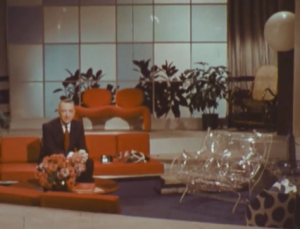 Walter Cronkite, sitting in the very orange living room of the future.