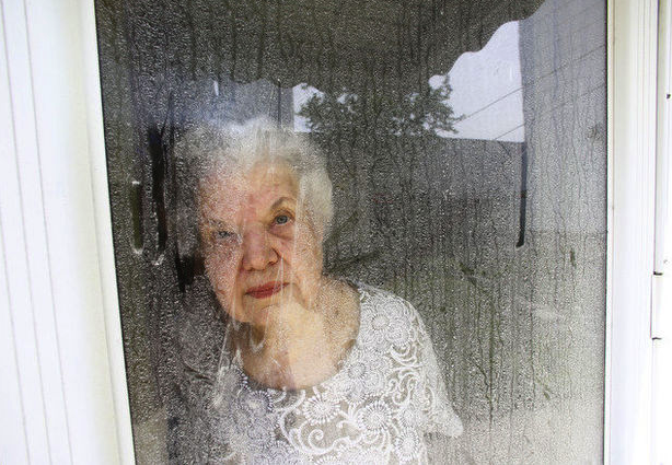 The homeowner, looking through her flour and cornmeal-crusted front door.  See more photos at NJ.com. (photo: William Perlman/Newark Star-Ledger)