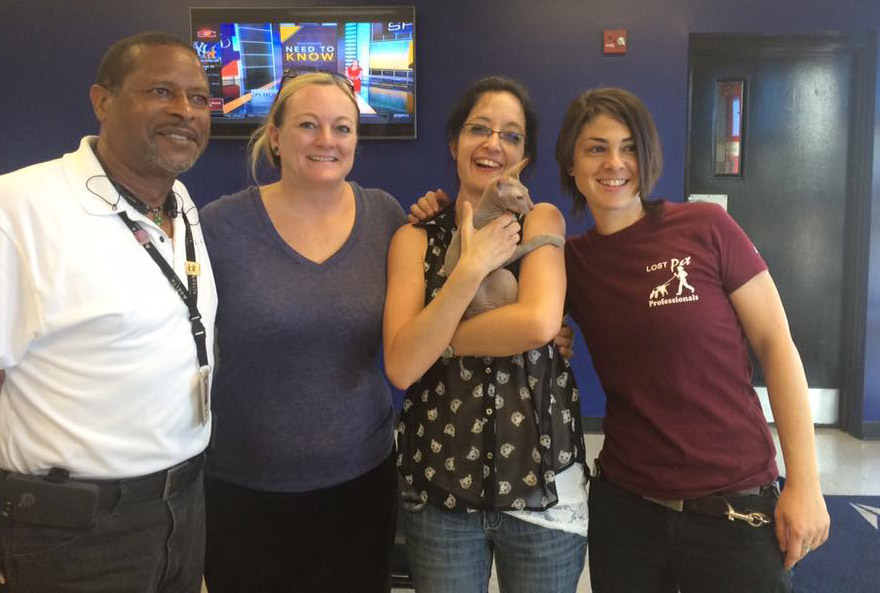 Rudy's family (center) and the Delta employee and pet detective who helped find the cat.